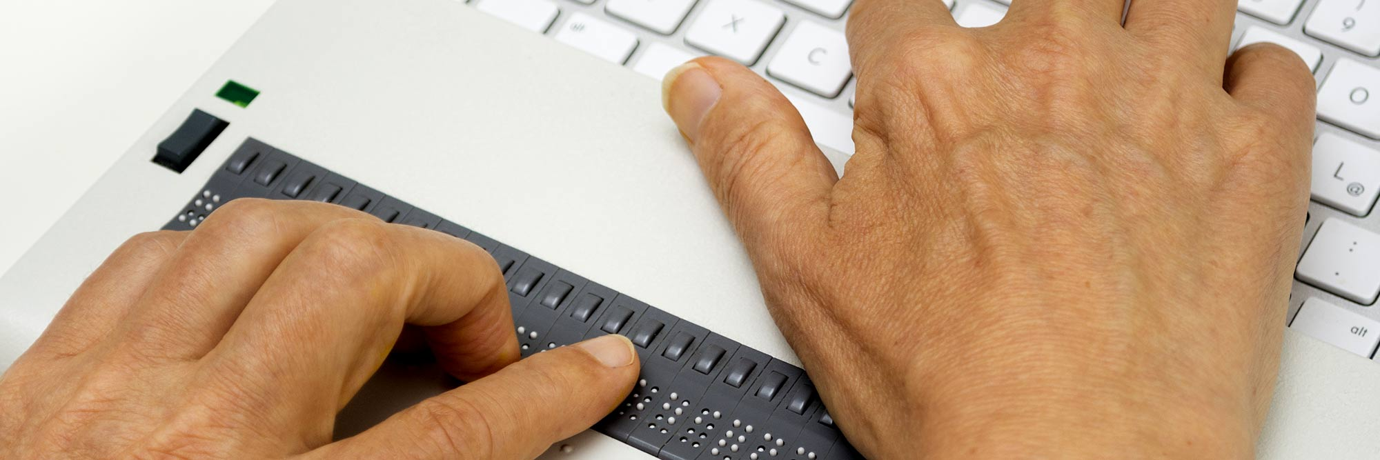 banner-assistive-technology-certificate Close up of a person's hands using a refreshable braille machine with a computer.