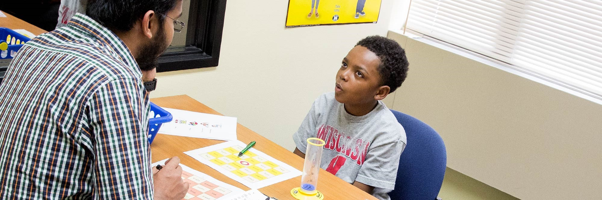 banner-communication-sciences-disorders-bs A student clinician does a word-retrieval task with his young client.