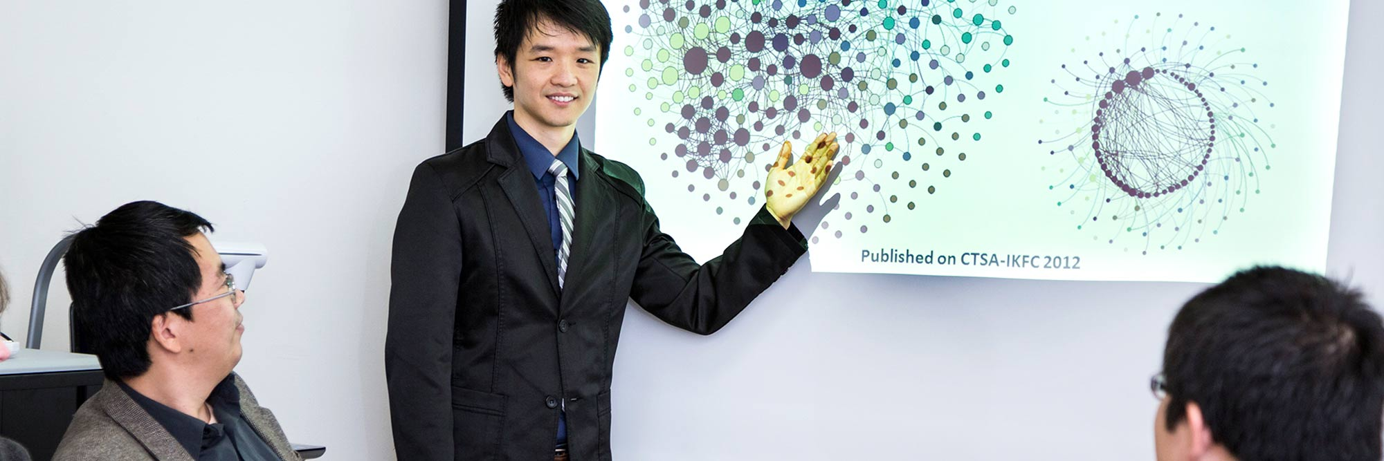 banner-health-care-informatics-ms BioDLP Center Director, Jake Luo, points to a PowerPoint slide on a screen that shows the relationship analysis of UWM and other healthcare institutions.