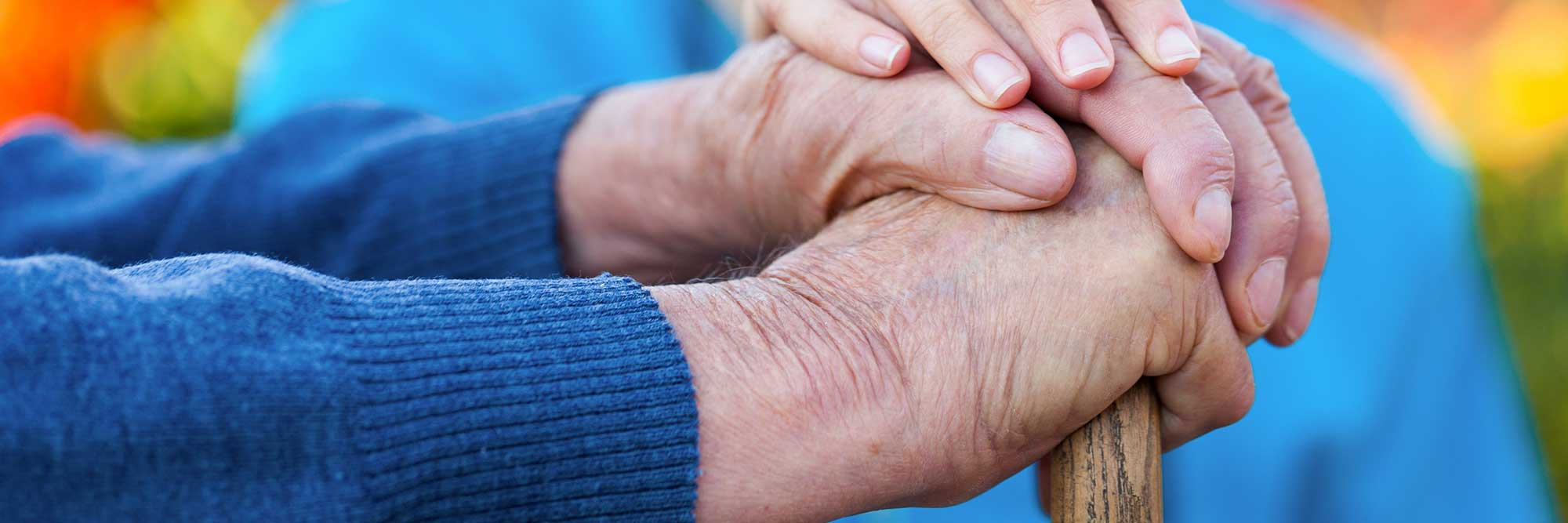 banner-health-sciences-applied-gerontology An older adult man's hands rest on the top of a wooden cane, while a young caregiver's hand gently rests atop of his hands.