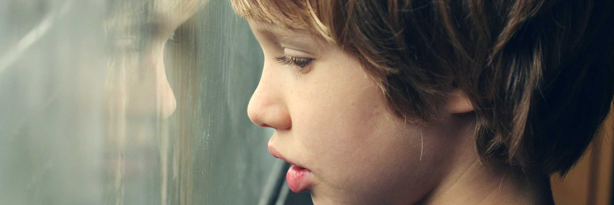 banner-health-sciences-trauma-informed-care A young boy looking out of a window.