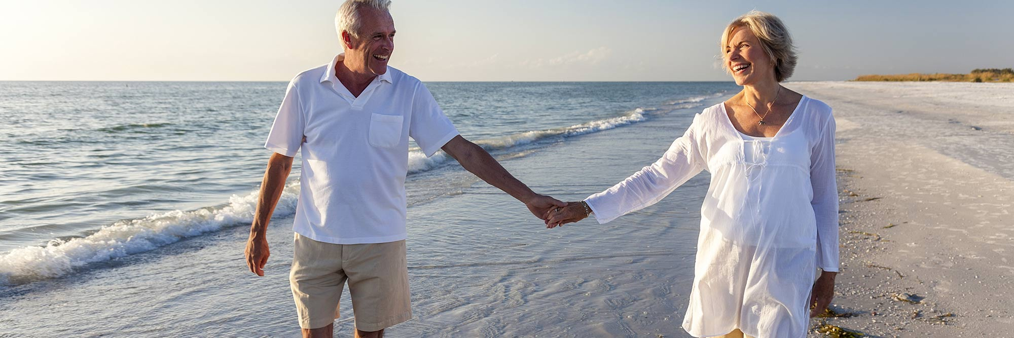 banner-healthy-aging-certificate Senior couple takes a walk on the beach hand-in-hand.