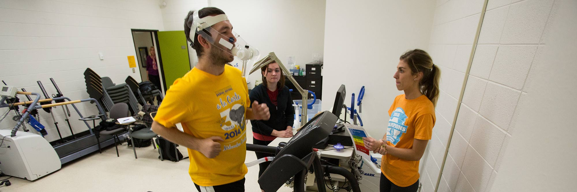 banner-kinesiology-minor BS A student on a treadmill with two other students monitoring.
